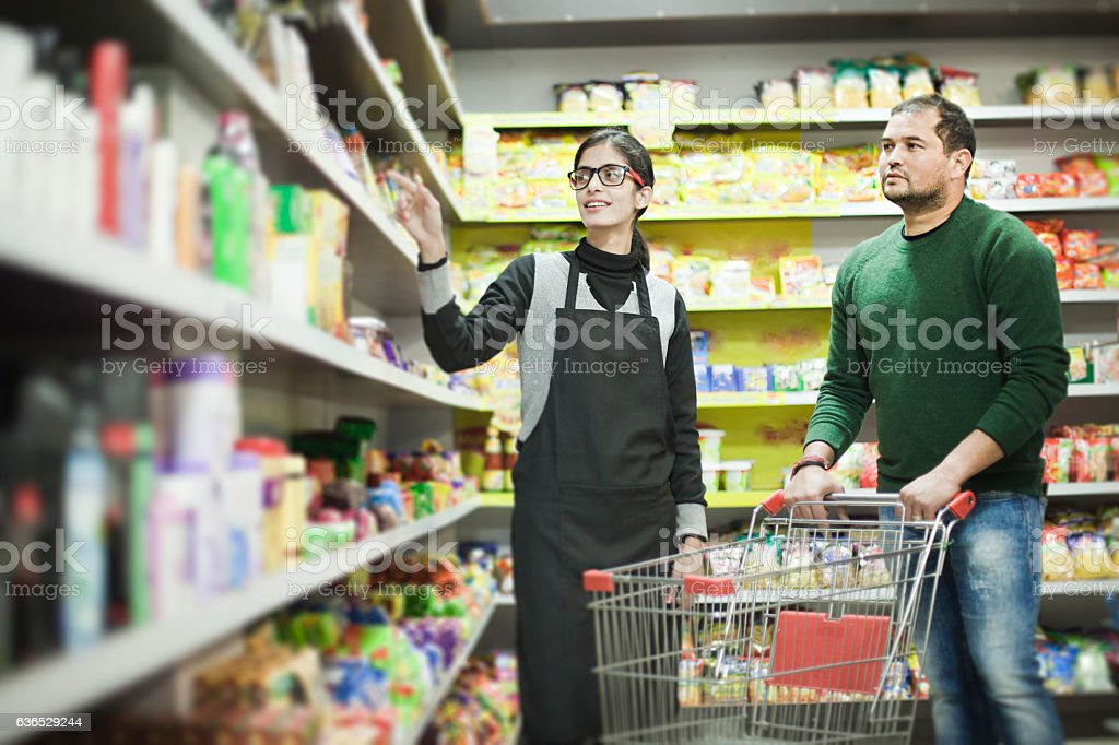 Asian young man shopping at supermarket and female staff helping. stock photo