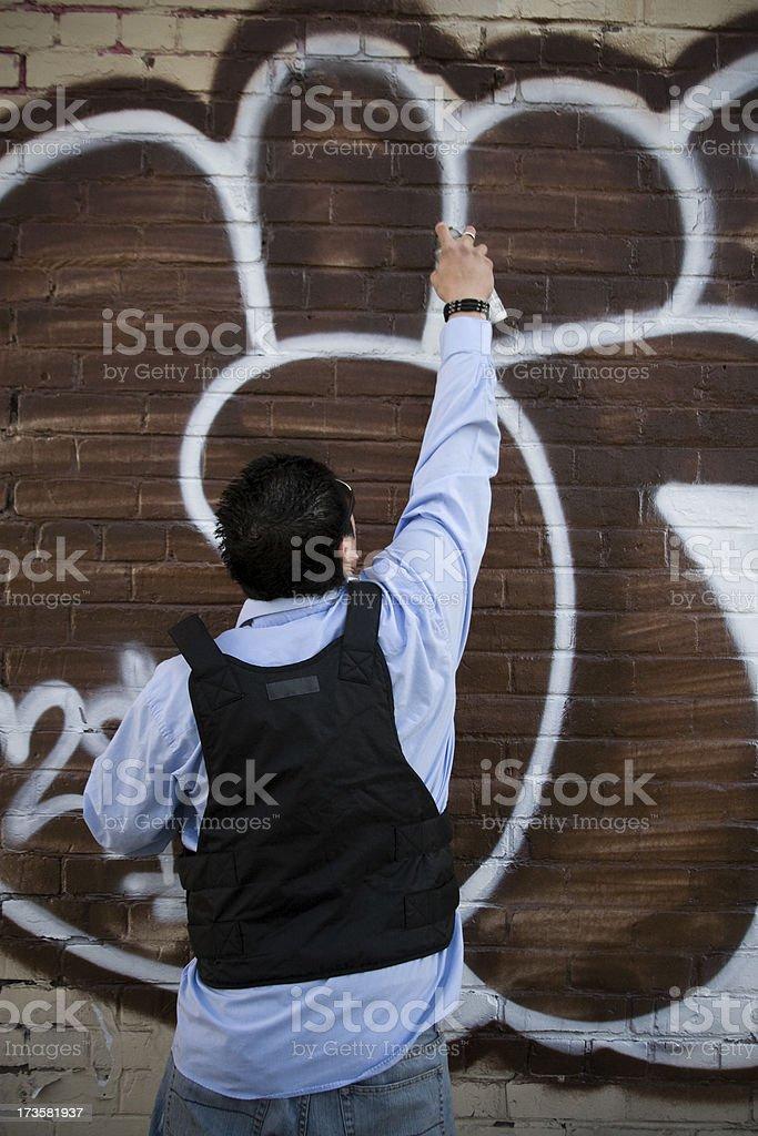 Asian Young Man Spraying Graffiti on Urban Brick Wall, Copyspace stock photo