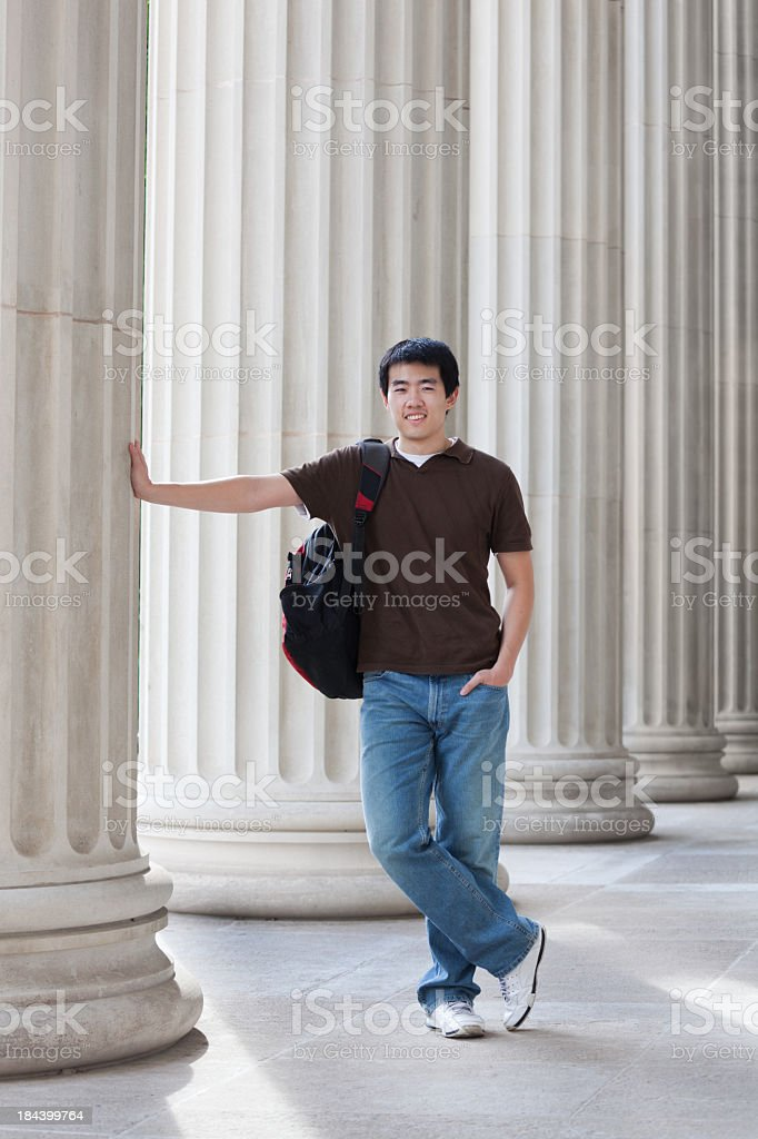 Asian Young Man, University Student by Campus Column Carrying Backpack stock photo