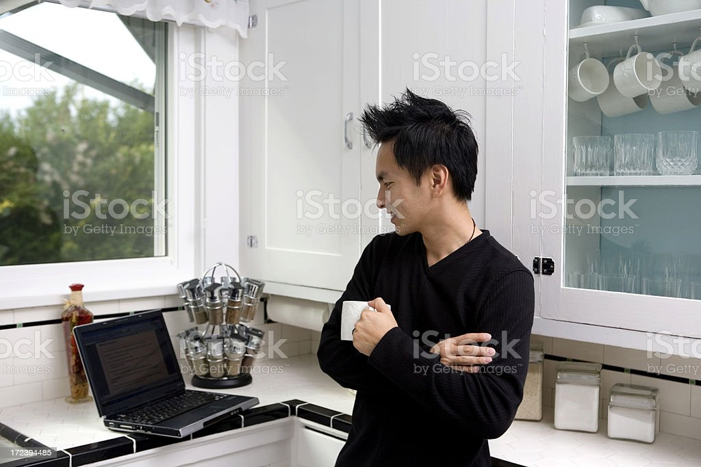 Asian Young Man Using Laptop in Domestic Kitchen, Smiling, Copyspace royalty-free stock photo
