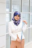 Asian Young Muslim woman headscarf measuring tape