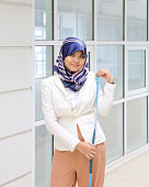 Asian Young Muslim woman headscarf measuring tape