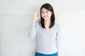 Asian young woman showing OK gesture