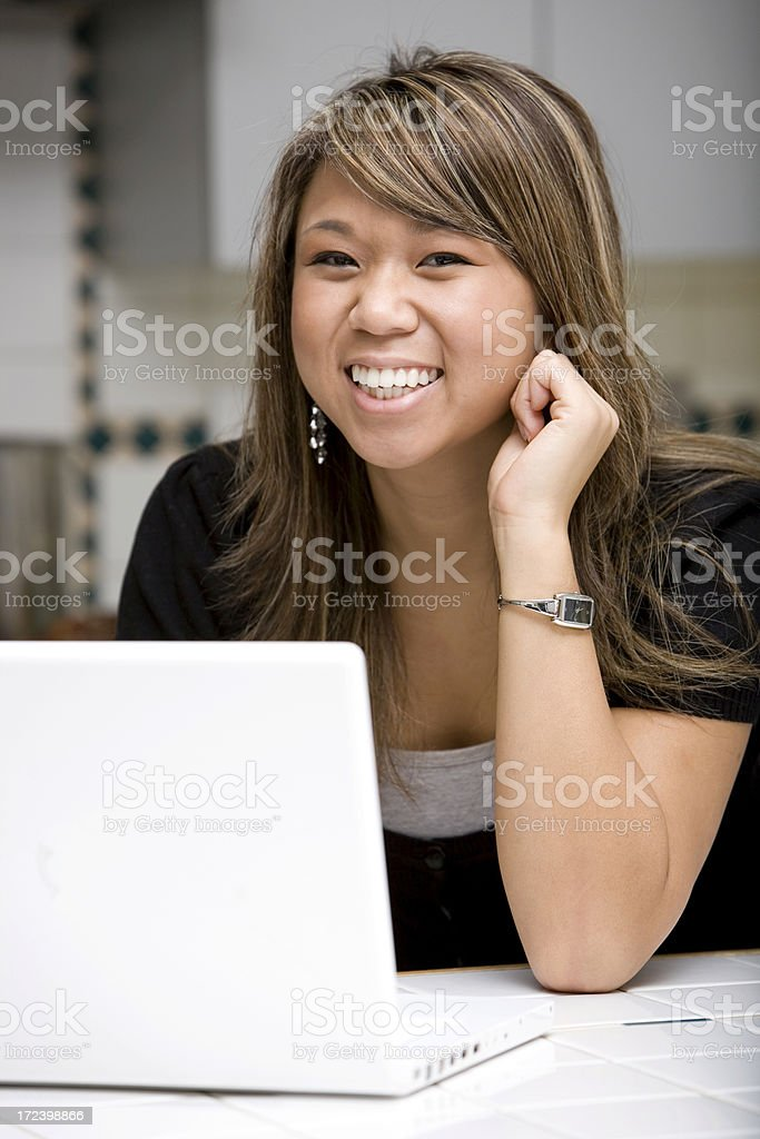 Asian Young Woman Smiling at Camera, Using Laptop in Home royalty-free stock photo