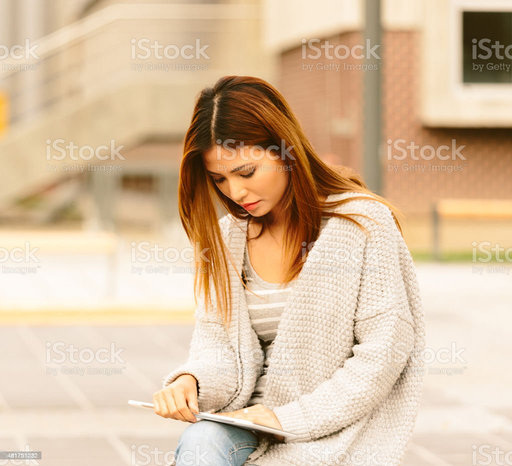 Asian young woman using digital tablet outdoor stock photo
