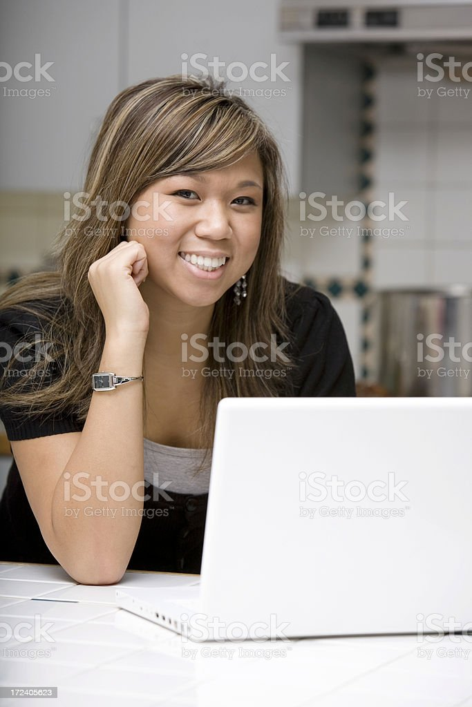 Asian Young Woman Using Laptop in Home Kitchen, Copy Space royalty-free stock photo