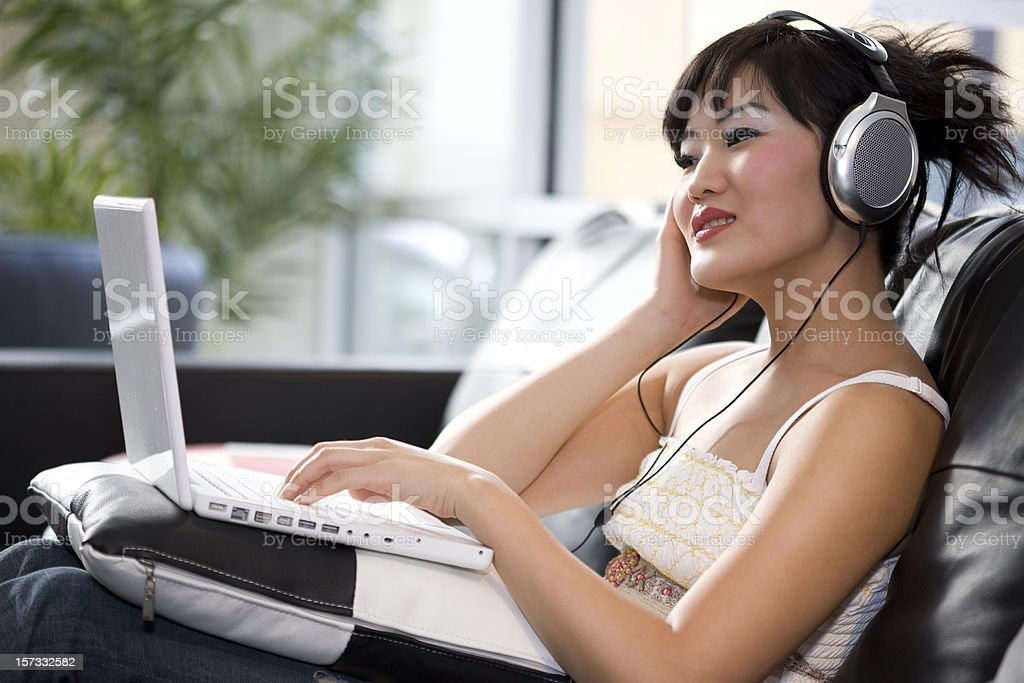 Asian Young Woman Using Laptop with Headphones, Copy Space royalty-free stock photo