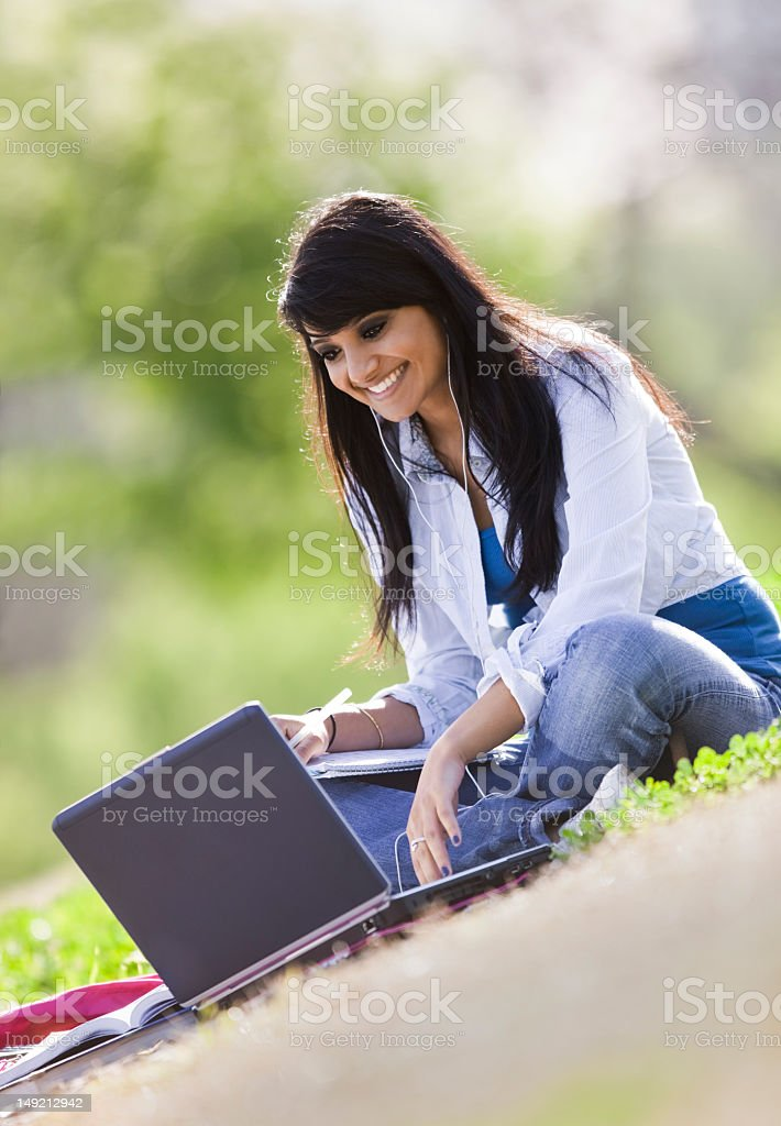 Asian-Indian Female Outdoors Smiling and Studying royalty-free stock photo