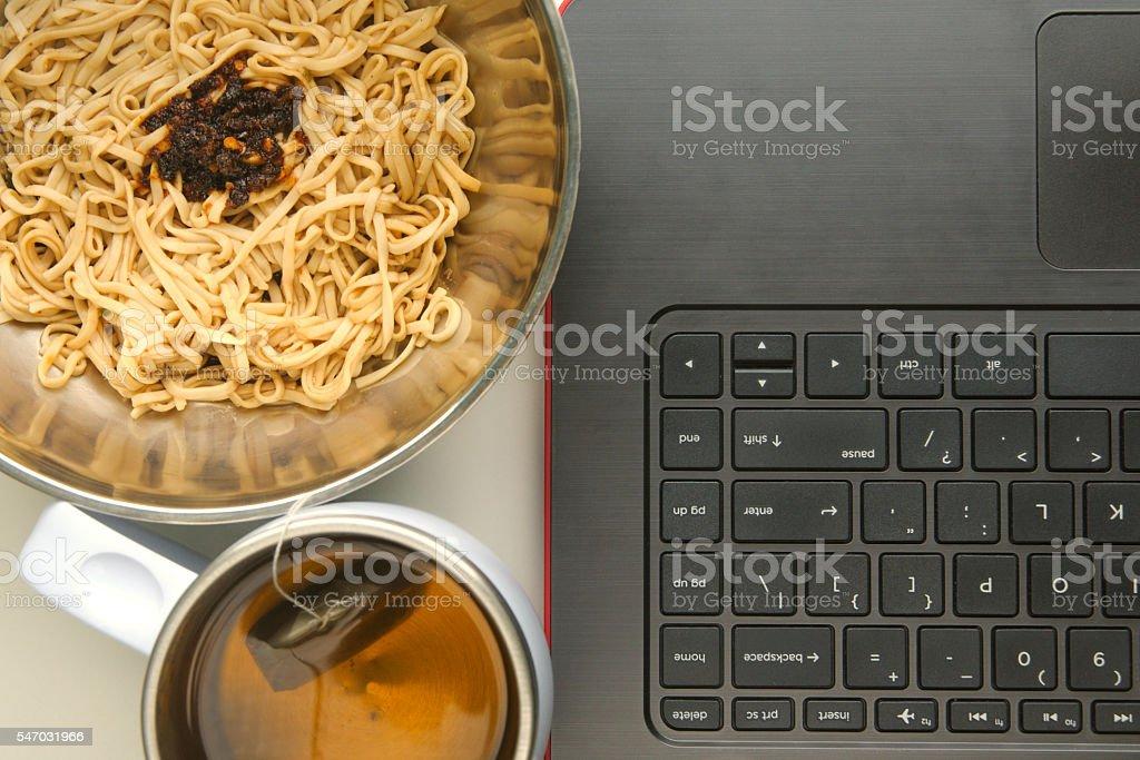 Asian-style instant noodles and tea next to a laptop foto de stock libre de derechos