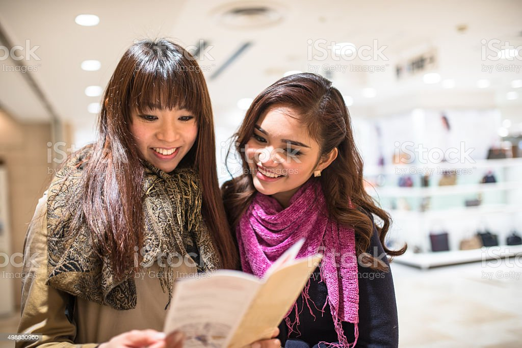 Asiatic friends togetherness on Tokyo reading the metro map stock photo