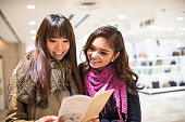 Asiatic friends togetherness on Tokyo reading the metro map
