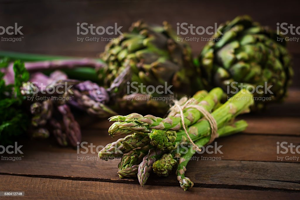 Asparagus and artichokes with herbs on a wooden background stock photo