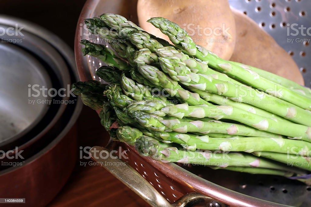 Asparagus and Potatoes in Copper Colander royalty-free stock photo