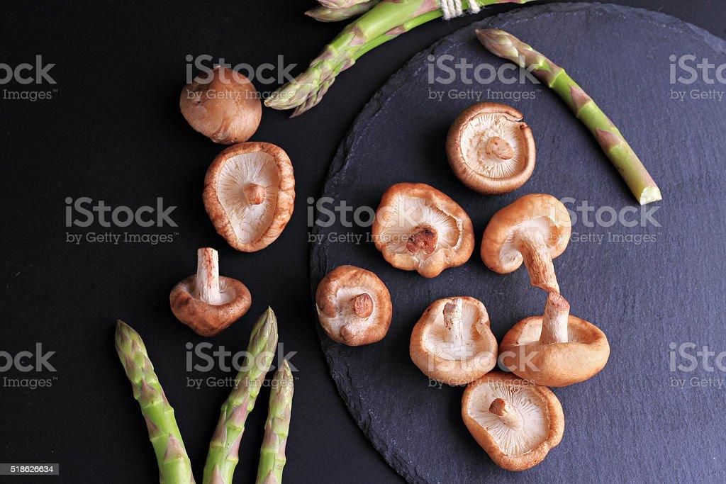 Asparagus and Shiitake mushrooms on black background. stock photo