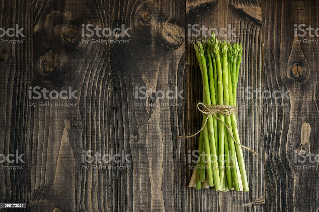 Asparagus bunch on a wooden background stock photo