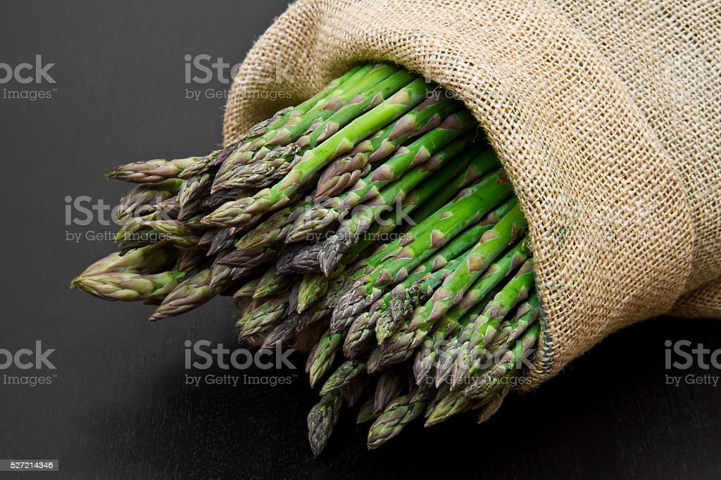 asparagus in burlap sack on wood stock photo