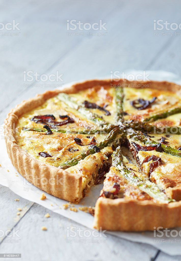 Asparagus quiche on white wooden surface stock photo