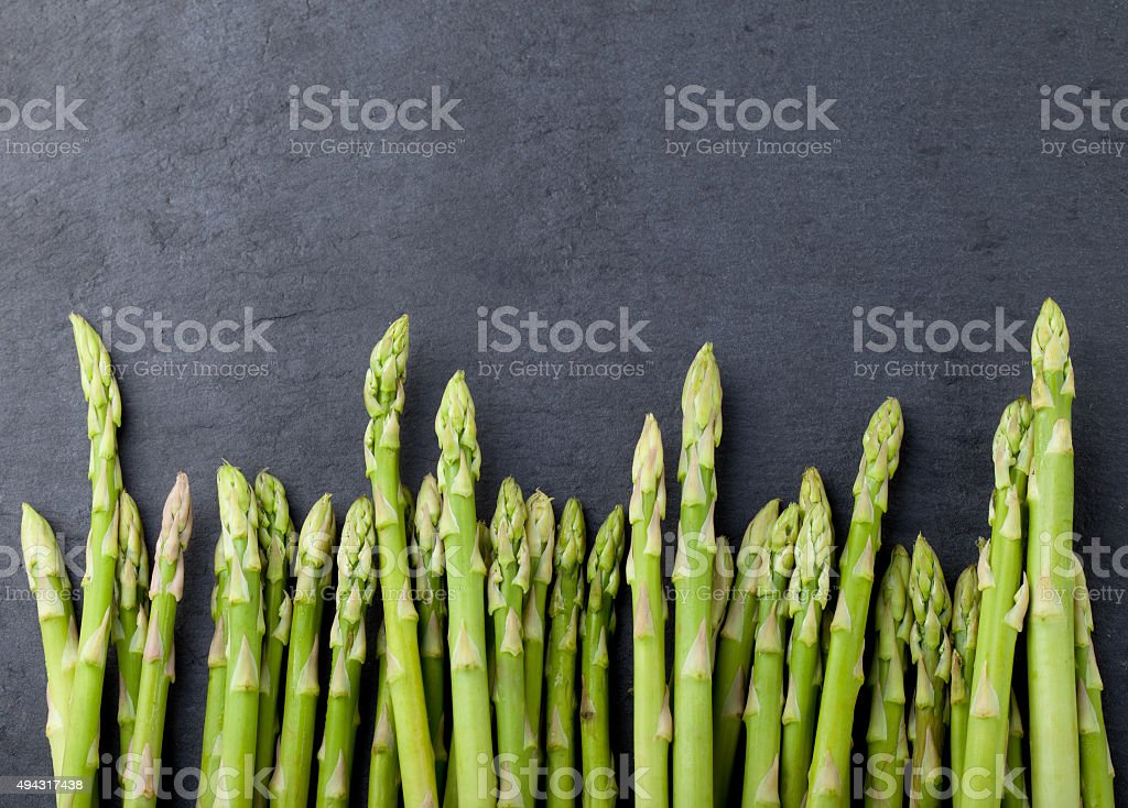 Asparagus sprouts on a black stone background. stock photo