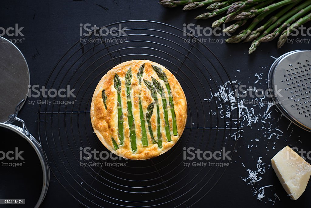 Asparagus tart with egg and cheese filling on cooling rack stock photo