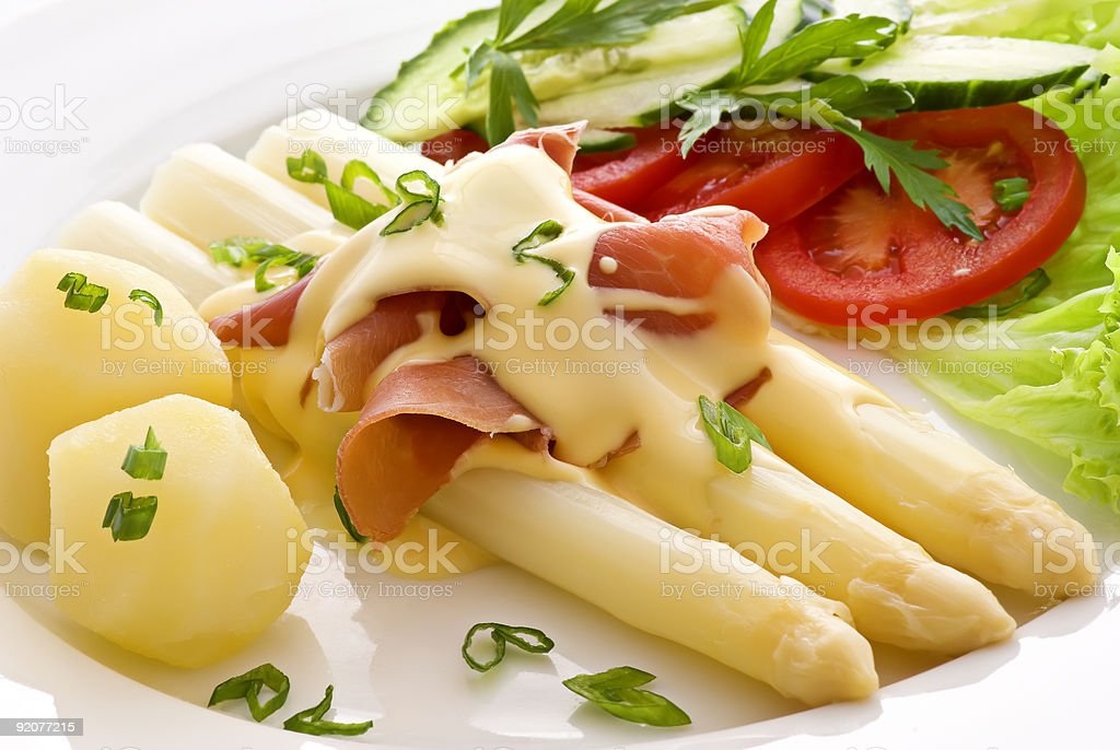 Asparagus with ham potatoes and salad on white plate royalty-free stock photo