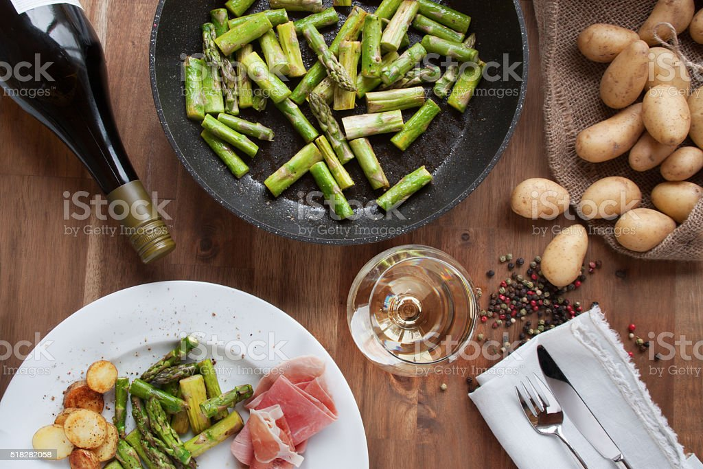Asparagus with ham potatoes, and wine stock photo