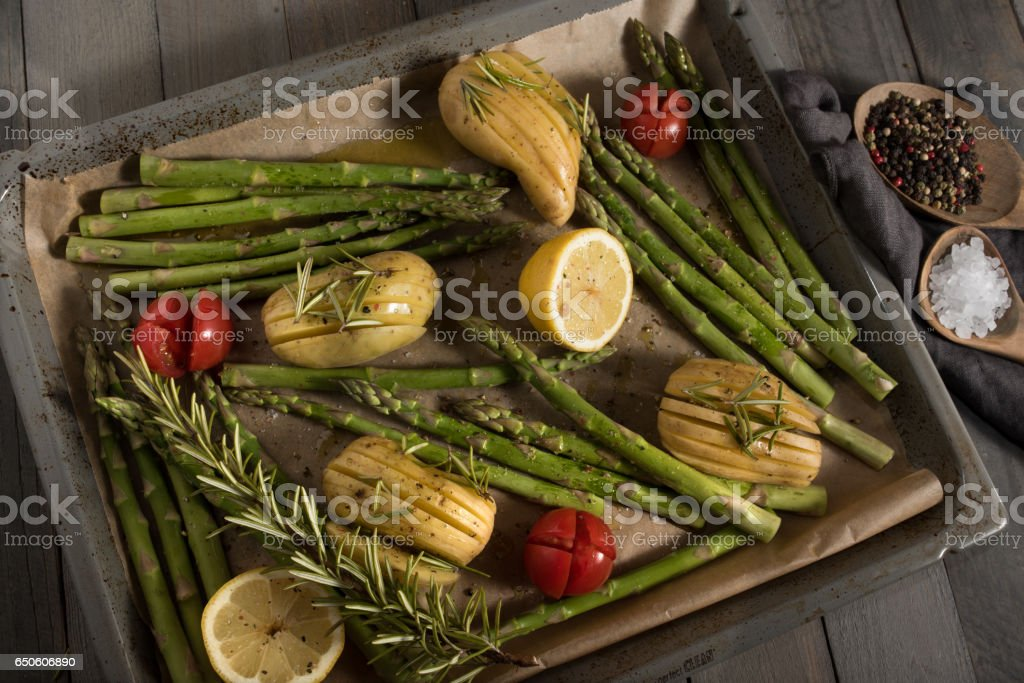 Asparagus with ingredients on a baking sheet stock photo