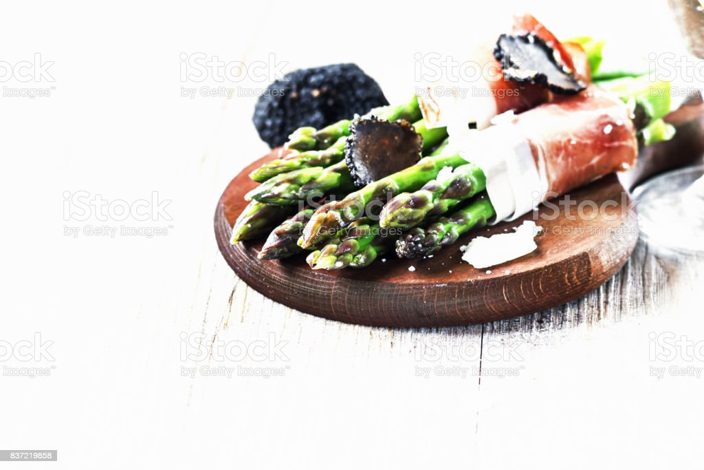 Asparagus with speck smoked ham and black truffle on a wooden board. Selective focus. stock photo