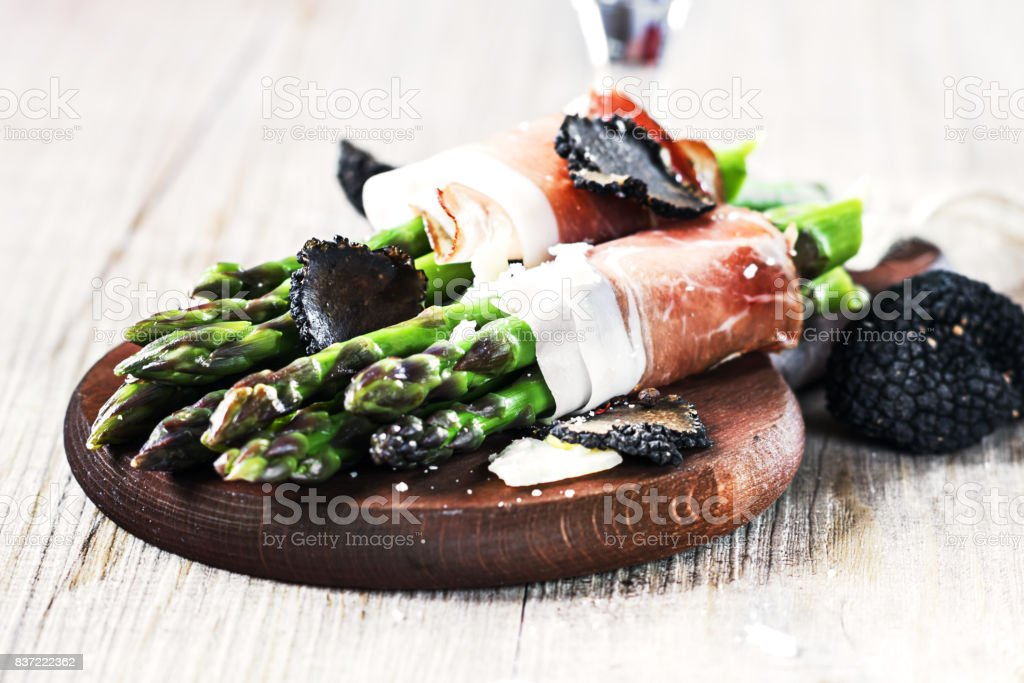 Asparagus with speck smoked ham and black truffle on a wooden board. stock photo