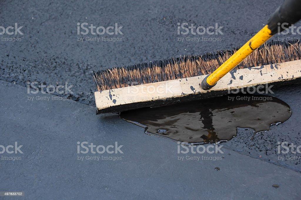 Asphalt Driveway sealing with brush stock photo
