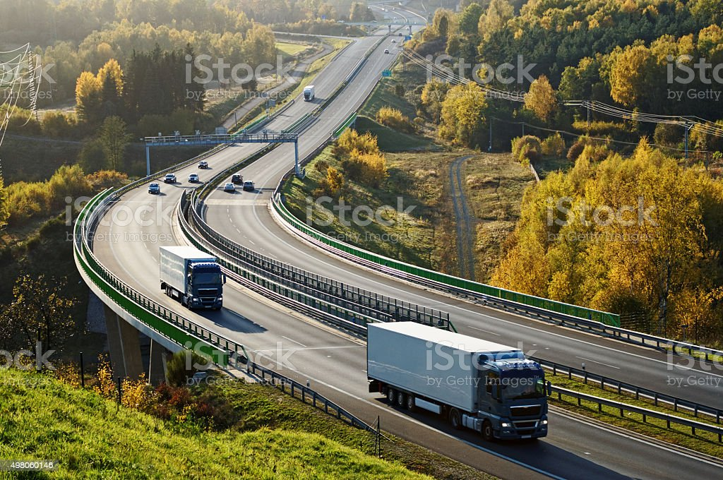 Asphalt highway with electronic toll gates in autumn woodland stock photo