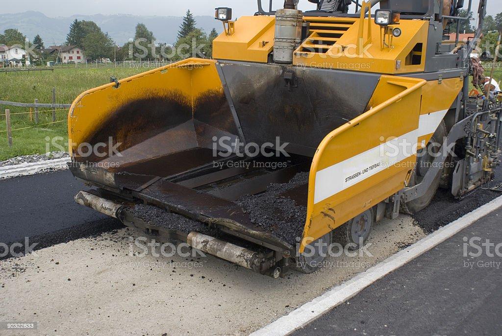 Asphalt paving machine at a construction site stock photo