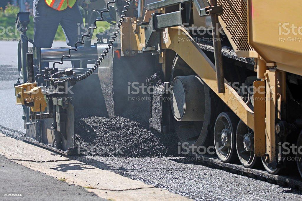 Asphalt Paving Machine At Work, Closeup View stock photo