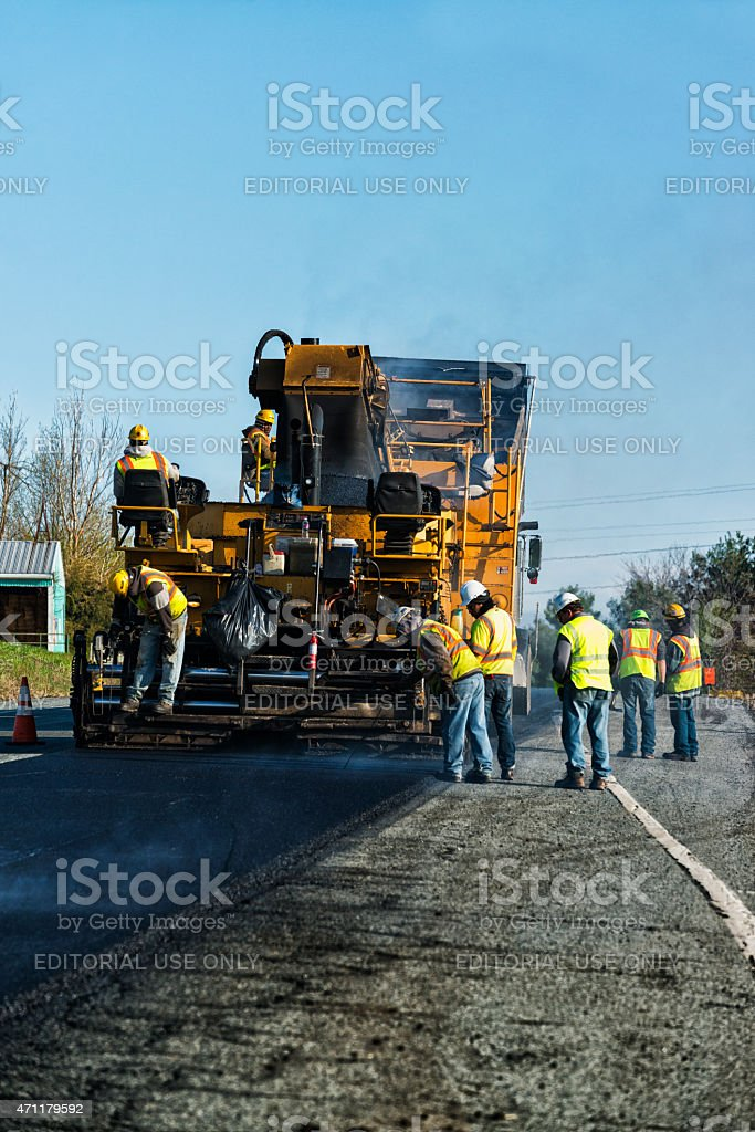 Asphalt paving machinery  resurfacing an old worn road stock photo