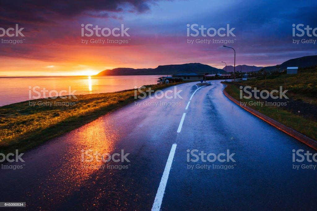Asphalt road along the sea at sunset Iceland stock photo