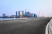 Asphalt road and modern cityscape at night in Shanghai