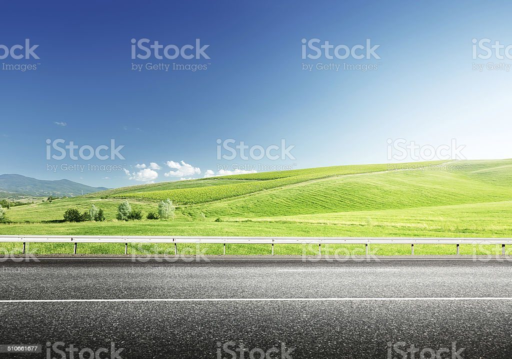 asphalt road and perfect green field stock photo