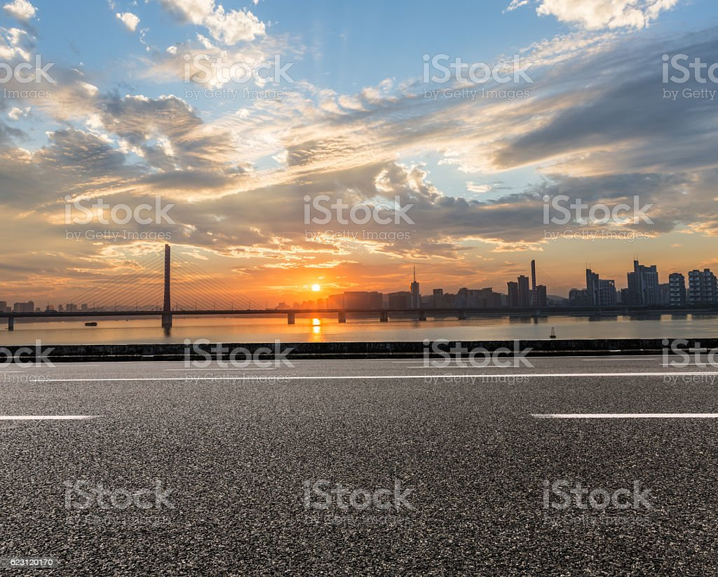 Asphalt road and the beautiful urban skyline stock photo
