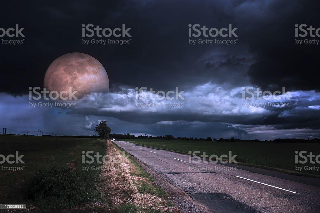 Asphalt road at night with moon stock photo