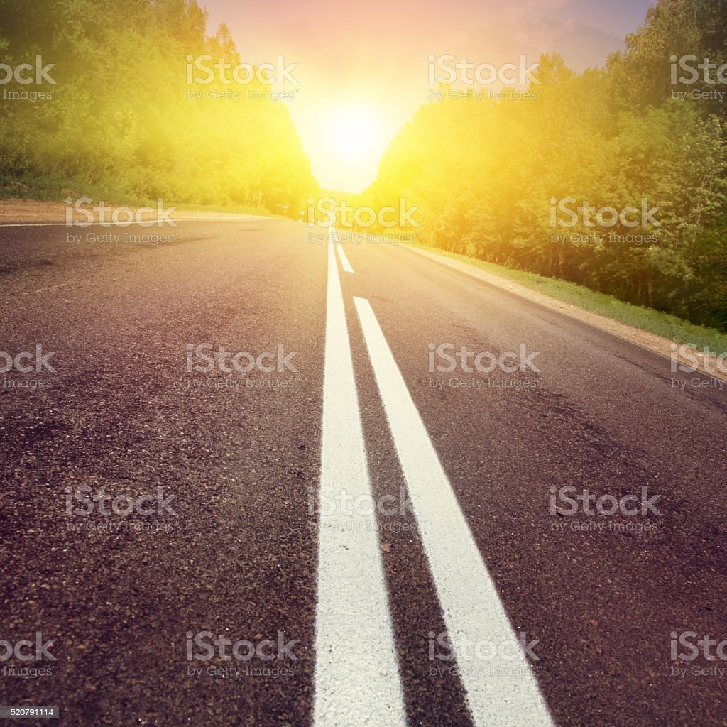 Asphalt road at sunset. stock photo