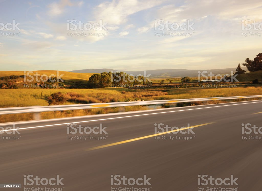 Asphalt road beside grassland at sunset stock photo