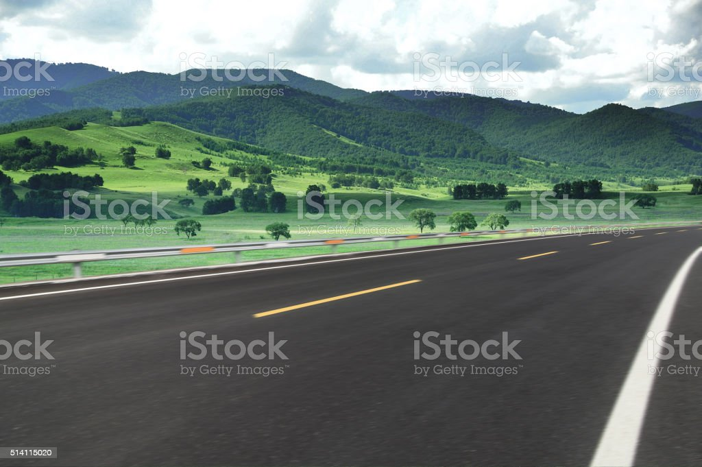 Asphalt road beside green meadow stock photo