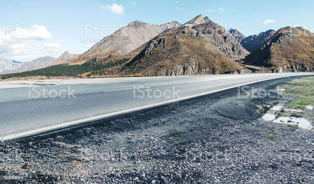 Asphalt road go by the mountains in alaska stock photo