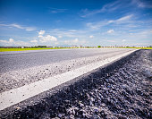 Asphalt road go through the rice paddy in summer