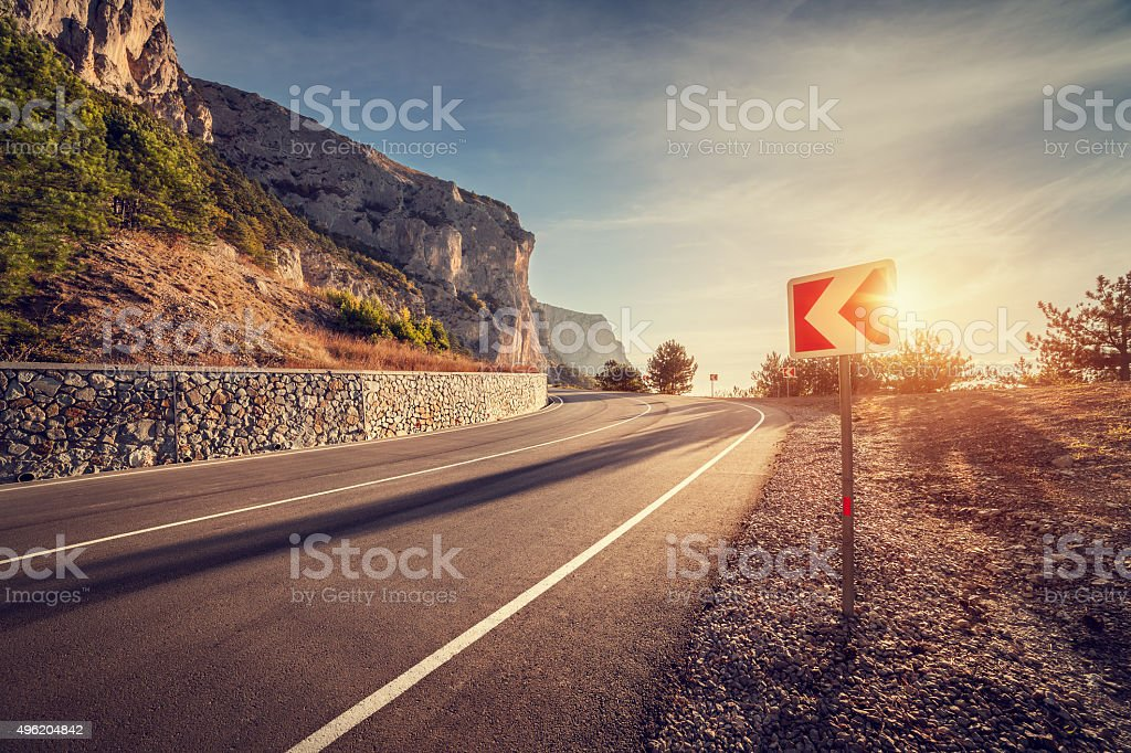 Asphalt road in autumn forest at sunrise and road sign stock photo