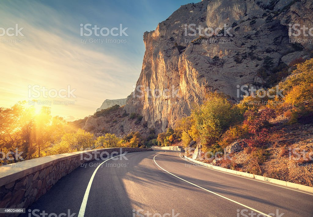 Asphalt road in autumn forest at sunrise. Crimean mountains stock photo
