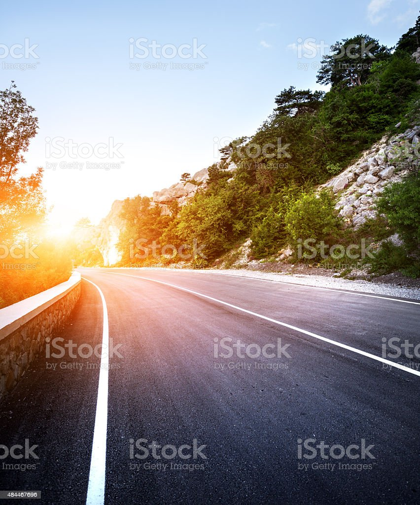Asphalt road in summer forest at sunset. Crimean mountains stock photo