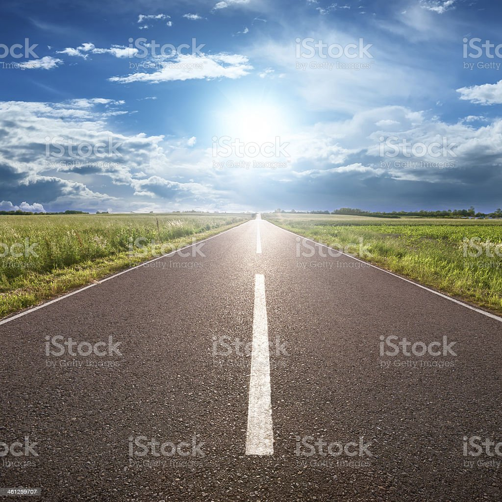 Asphalt road leading to horizon with grass and blue sky stock photo