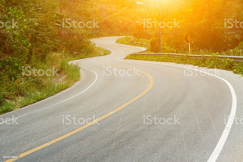 Asphalt road sharp curve along with tropical forest. stock photo