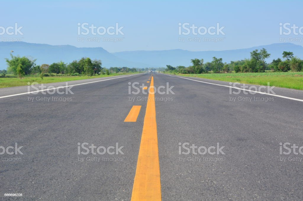 asphalt road through the green field and clouds on sky stock photo