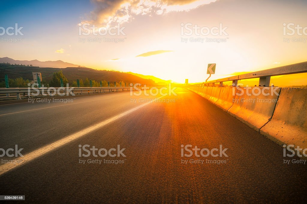 Asphalt road with Blurred Motion at sunset stock photo
